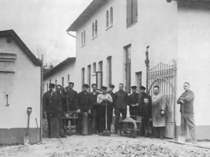 Schwarz-Weiß-Foto von einer Gruppe Männern vor einem Bauplatz.