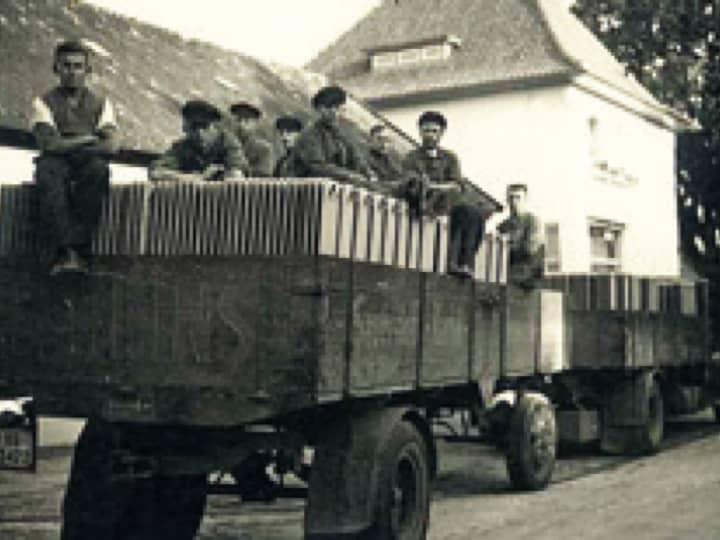 Schwarz-Weiß-Foto von ein paar Arbeitern, die auf einem mit Heizungen beladenen Anhänger-Wagen sitzen.