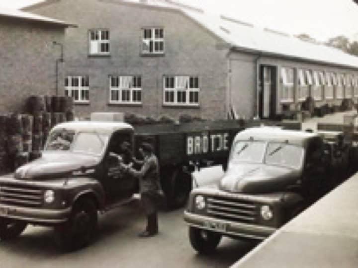 """Schwarz-Weiß-Foto von einem BRÖTJE Fabrikgebäude mit zwei großen Autos davor, eines mit Anhänger mit der Aufschrift """"BRÖTJE""""."""