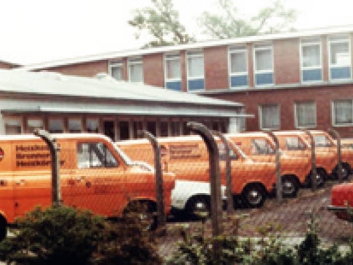 Foto von einem BRÖTJE Firmengebäude von Außen, davor einige BRÖTJE-Wägen in Orange.