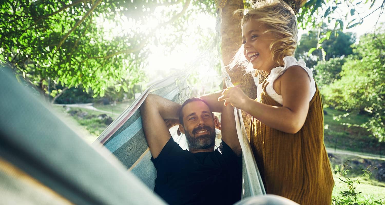 Eine glückliche Familie, Eltern, kleine Tochter und junger Sohn, gehen im Grünen zum Picknicken.
