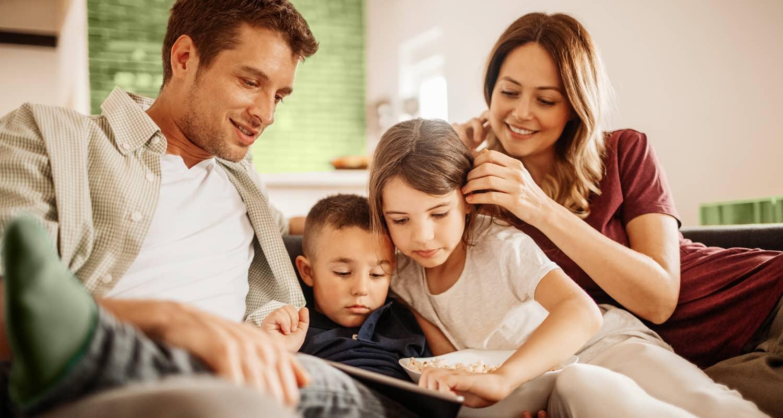 Fröhliches Familienleben im schönen Eigenheim. Die Mutter hält die kleine Tochter auf dem Schoß, der Vater macht mit dem jungen Sohn im Arm Spaß.