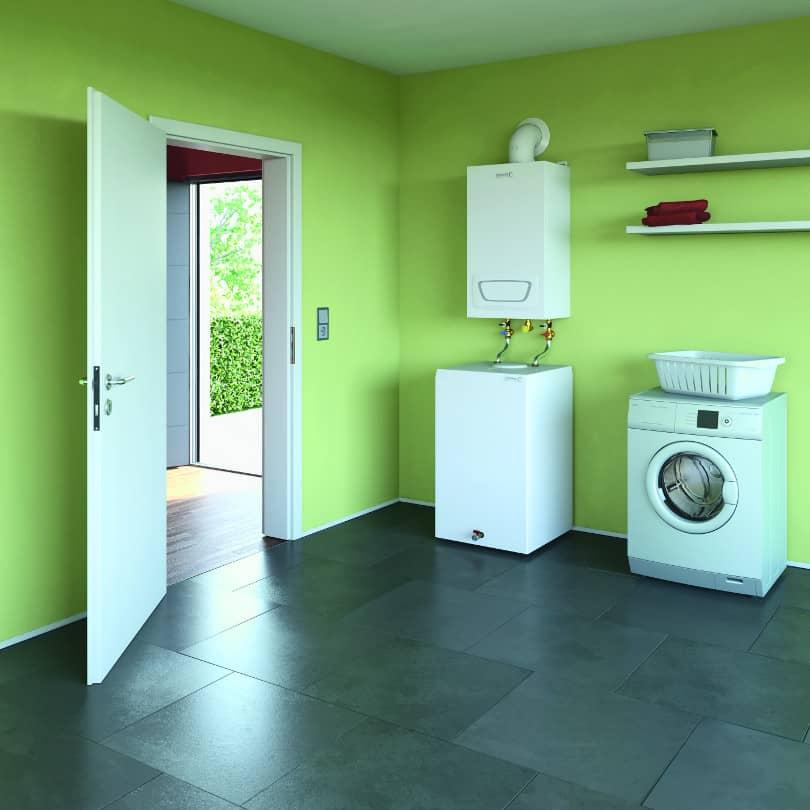 Der Gasheizkörper WGB EVO befindet sich in einem grün gestrichenen Hauswirtschaftsraum, rechts davon eine Waschmaschine.