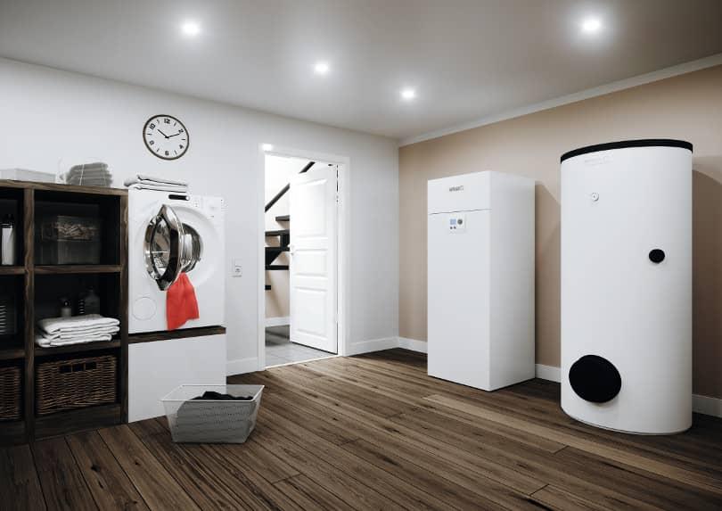 Die Wärmepumpe BSW NEO im mit Parkett verlegten Hauswirtschaftsraum. Links davon Waschmaschine und ein Regal.