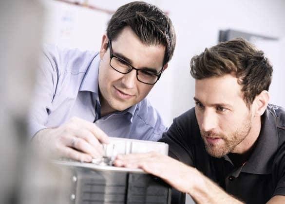 Zwei Männer schauen sich ein Gerät genau an.