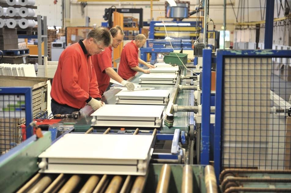 3 Männer arbeiten am Fließband in einer Fertigungshalle für Heizungen.