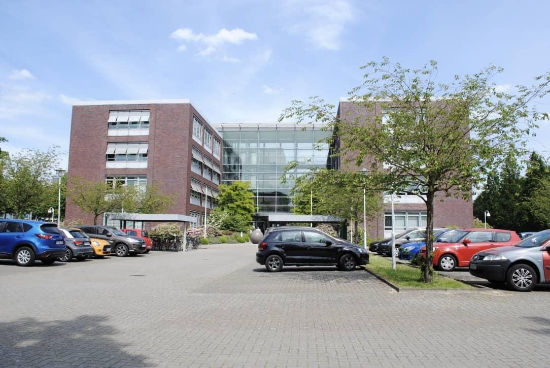 Ansicht eines Bürogebäudes mit Parkplatz davor.