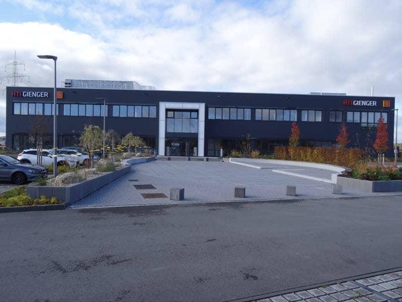 Front-Ansicht des Verwaltungsgebäudes in Röttenbach mit Eingangsbereich und Parkplatz.
