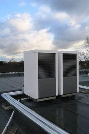 Zwei Luft- und Wärme-Wasserpumpen BWL NEO installiert auf flachem Hausdach