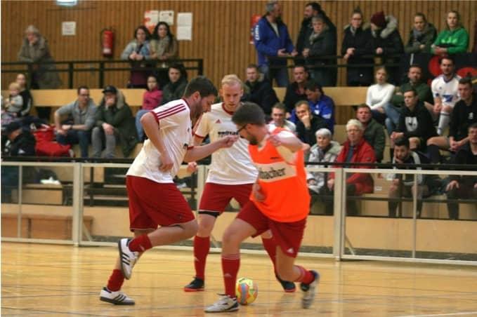 3 Fussballer kämpfen um den Ball, die Halle ist gefüllt
