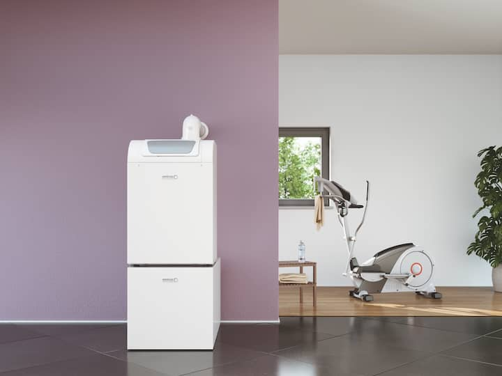 Brötje's BGB EVO gas condensing boiler is sitting in front of a lilac wall, with an exercise bike, window and a large houseplant in the background.