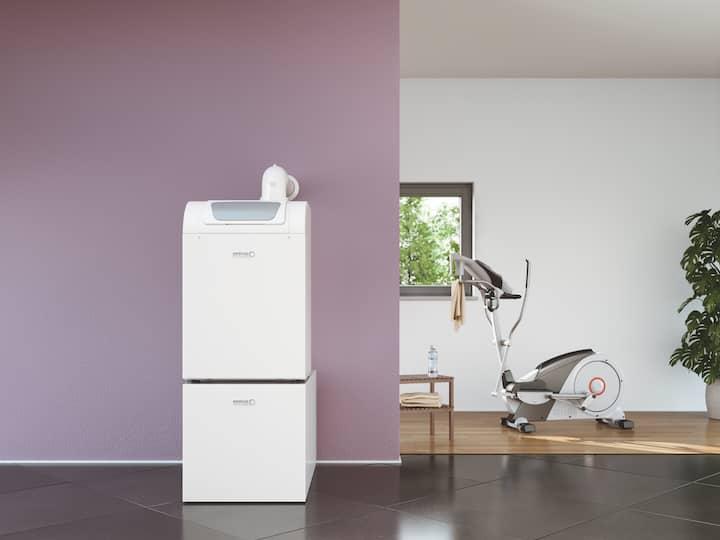 Der Gas-Brennwertkessel BGB EVO von Brötje steht vor einer fliederfarbenen Wand, im Hintergrund ein Hometrainer, Fenster und eine große Zimmerpflanze.