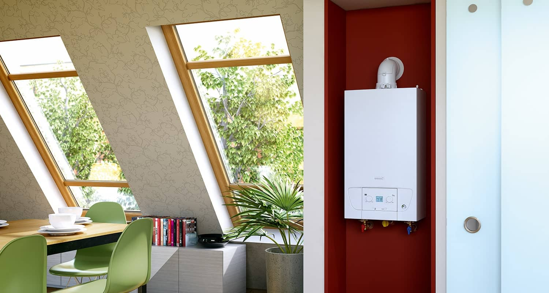 Die Gas-Brennwerttherme WLC und WLS, platzsparend in der Dachgeschosswohnung untergebracht auf rotem Hintergrund. Links davon ein helles, modern eingerichtetes Zimmer mit großem Tisch und grünen Stühlen.