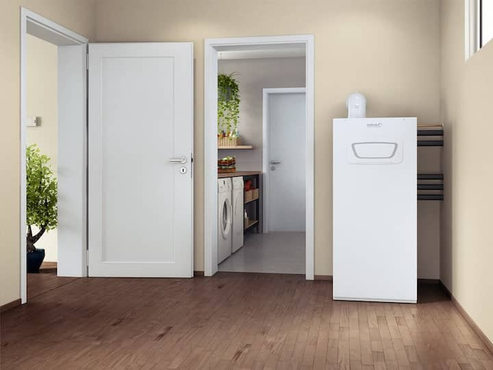 A Brötje BBK EVO gas heater in the entrance area of a detached house. To the left of this is a view to a utility room and an open front door to the outside.