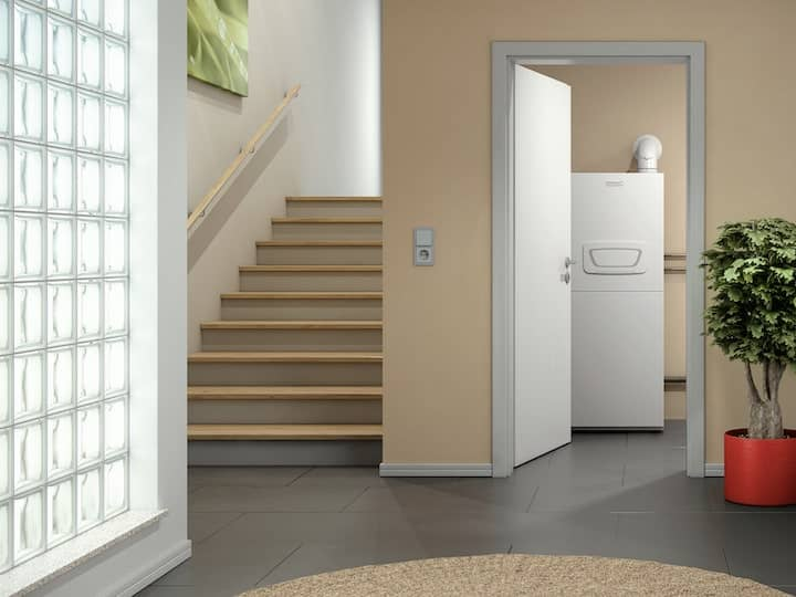 Blick auf die Brötje Gasheizung BBS EVO aus dem Hausflur in den Technikraum. Links ein Treppenaufgang, rechts eine große Zimmerpflanze.
