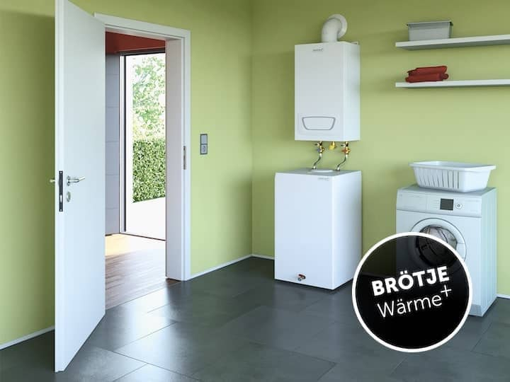 A gas condensing boiler in the light green painted laundry room of a detached house.