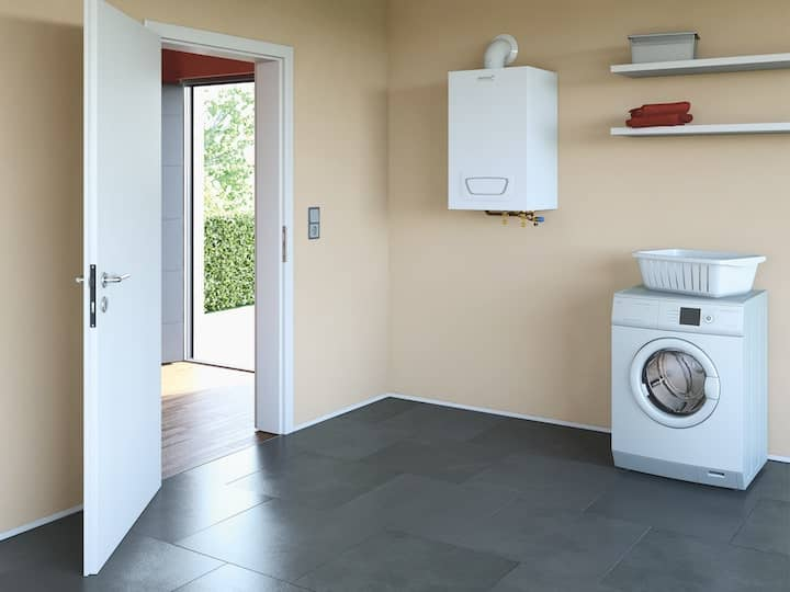 A gas-fired WGB-K EVO condensing boiler in a cream-coloured laundry room of a detached house.