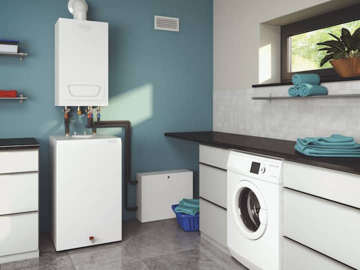 A gas condensing boiler in a turquoise-coloured utility room.