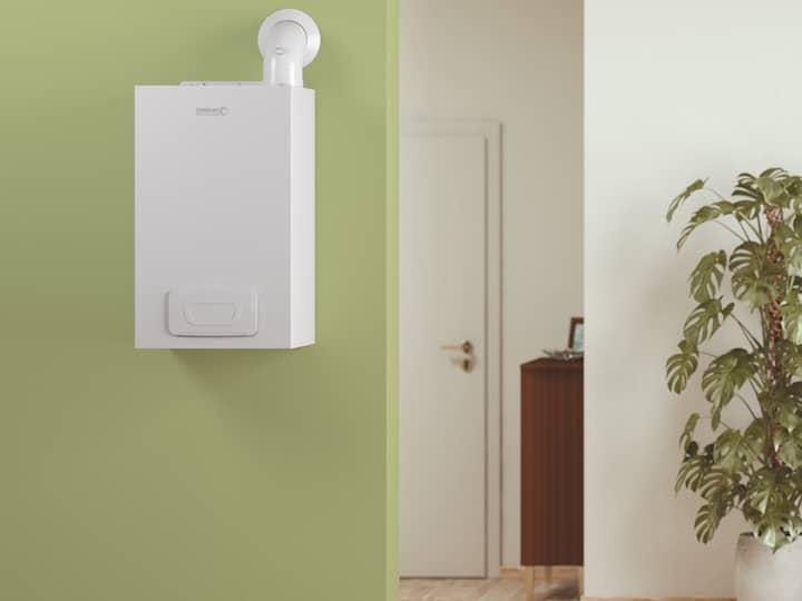 The wall hung boiler WHBK from BRÖTJE is mounted on a light green wall with a plant on the right.