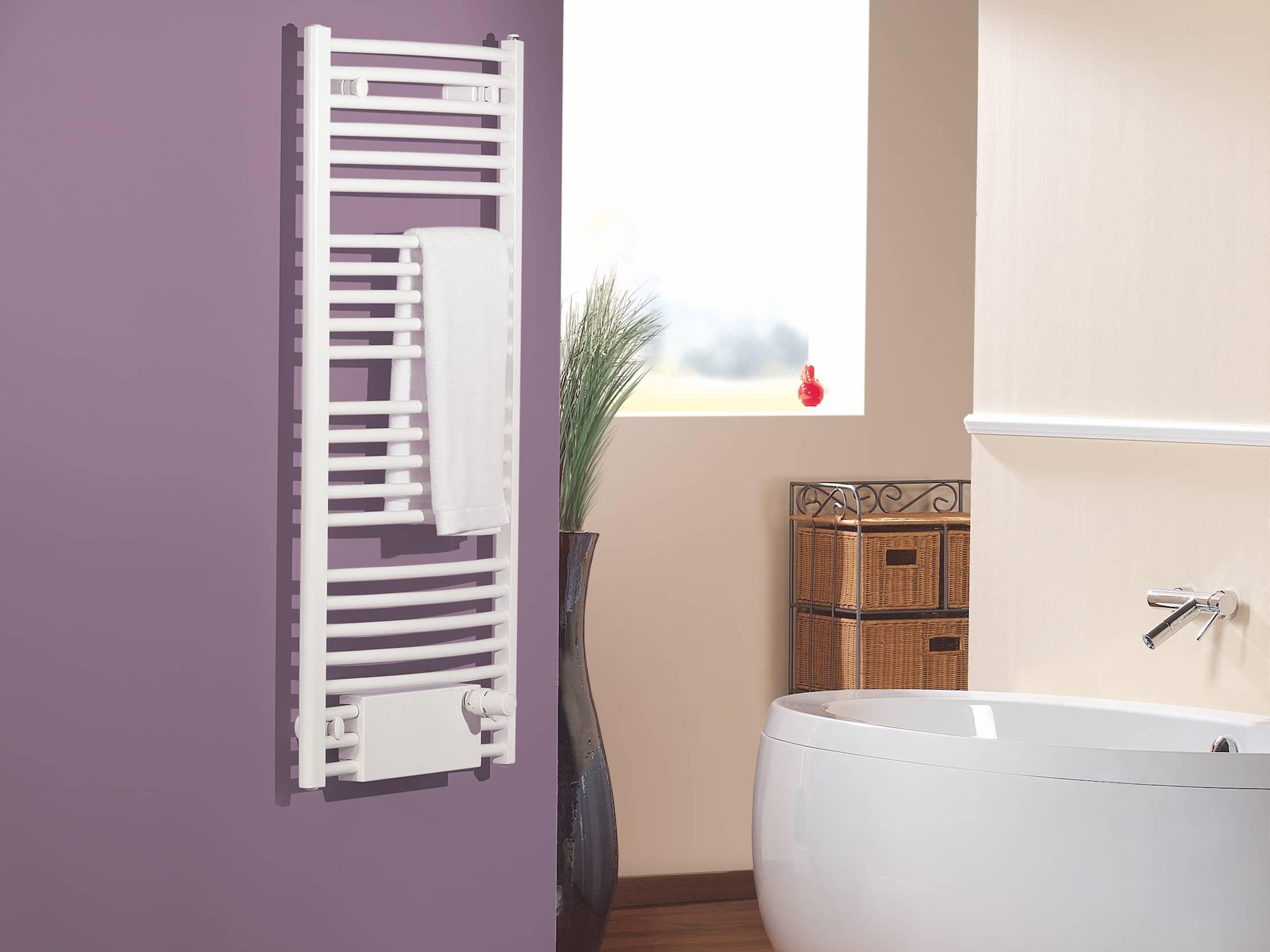 Der weiße Badheizkörper, montiert an der purpurroten Wand im Badezimmer eines Hauses.