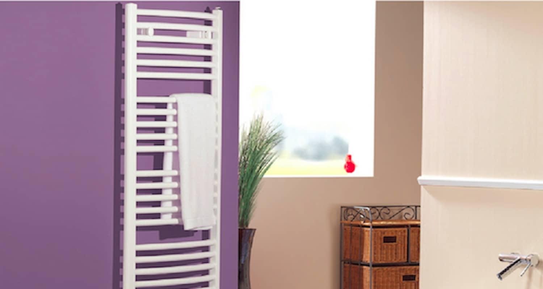 Ein weißer Flachheizkörper an hellgrauer Wand, rechts davon die Couch mit Tisch und Wandregal des Wohnzimmers.