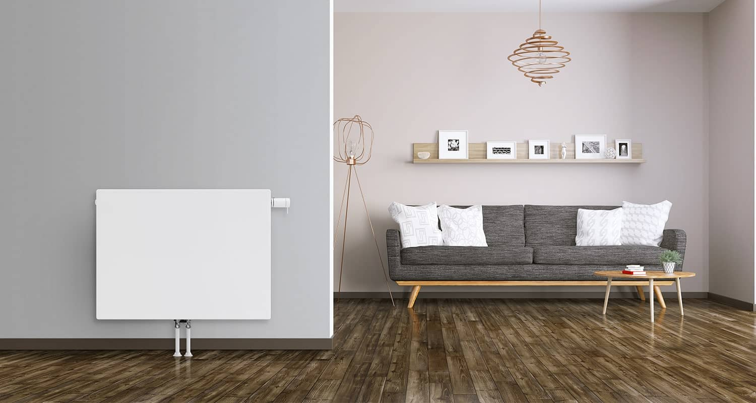 A white panel radiator on a light grey wall, to the right of which is a sofa, together with a table and wall shelving, in a living room.