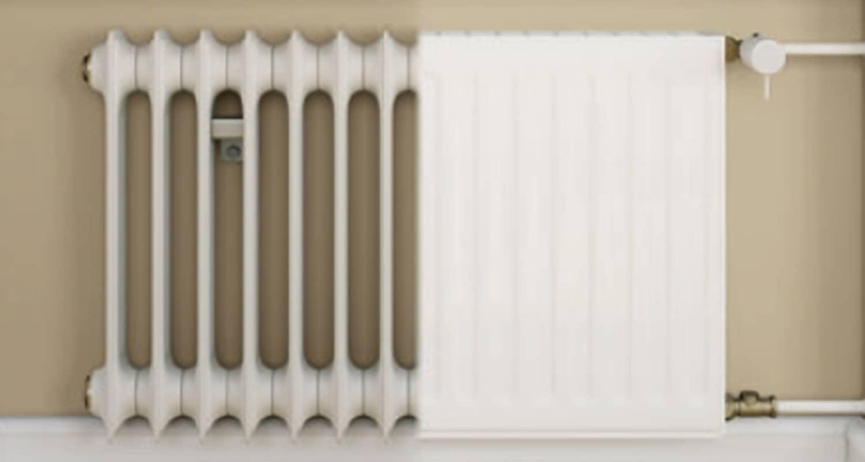 Ein weißer Flachheizkörper an einer hellgrauen Wand, rechts davon das Wohnzimmer mit Couch, Tisch und Wandregal.