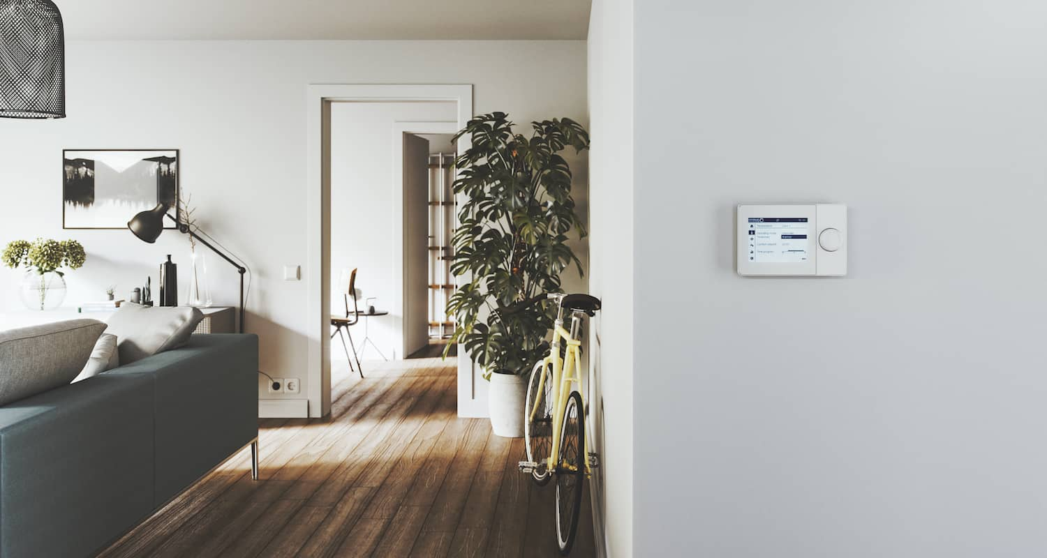 A ISR Plus control unit on a light grey wall. To the left is a cosy living room with a grey sofa, a large houseplant and a yellow bicycle leaning against a wall.
