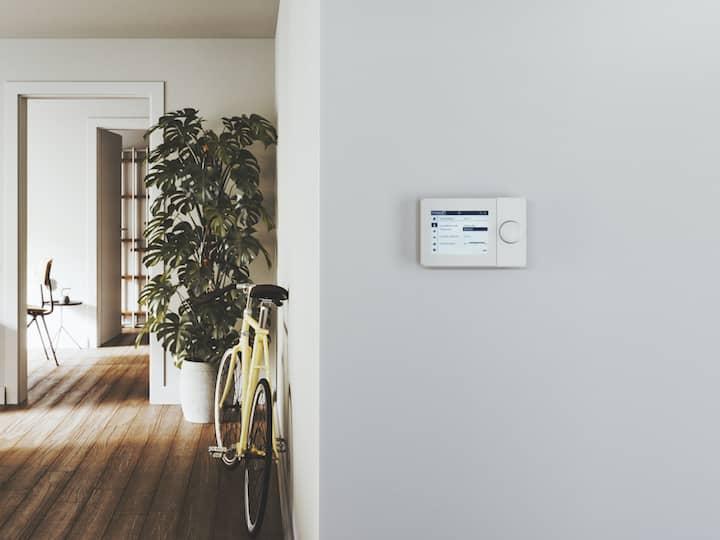 Die Regelung ISR Plus an einer hellgrauen Wand. Links davon das gemütliche Wohnzimmer mit grauem Sofa, großer Zimmerpflanze und einem gelben Fahrrad, das an der Wand lehnt.