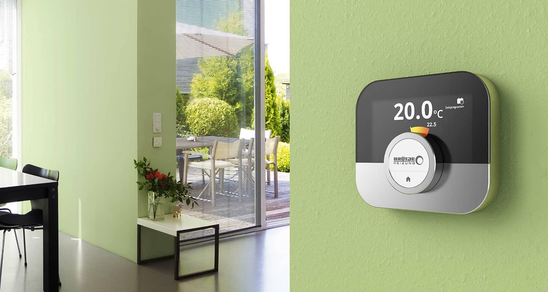 Die Regelung des Raumgerätes ISR IDA an einer grünen Wand im Wohnraum eines Hauses mit Blick in der Garten.