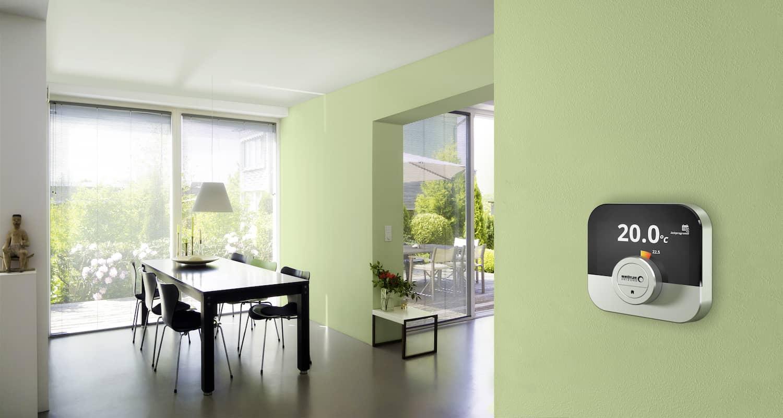 Die Regelung OT IDA ist ein einer hellgrünen Wand befestigt, dahinter sieht man das helle Esszimmer und Wohnzimmer mit Fenstern.