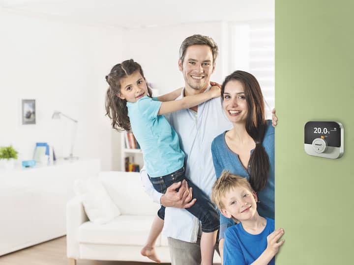 The IWR IDA unit control on a light green wall, on the right is a young family in front of a living room.