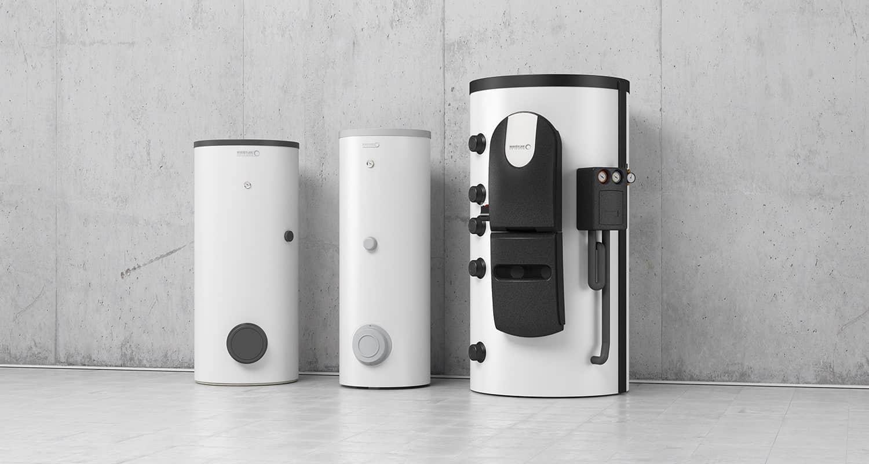 Drei Trinkwassererwärmer in verschiedenen Größen in weiß und dunkelgrau an einer Betonwand aufgestellt.