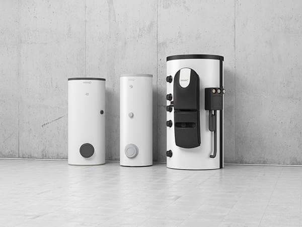 Three drinking water heaters in different sizes in white and dark grey placed on a concrete wall.