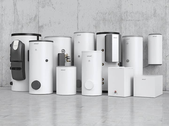 Trinkwassererwärmer in verschiedenen Größen in weiß und dunkelgrau an einer Betonwand aufgestellt.