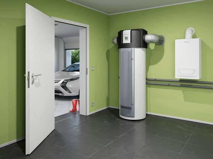 A BTW heat pump in a  boiler room, painted green, next to a garage.