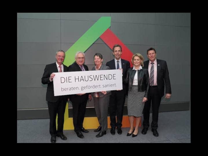 Vier Männer und zwei Frauen, in Anzügen gekleidet stehen vor einer dunkelgrauen Wand und halten ein großes, langes Schild in der Hand auf dem Hauswende, beraten, gefördert, saniert steht.