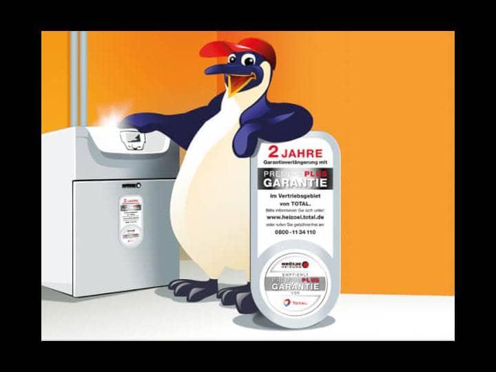 Ein Pinguin mit roter Mütze steht zwischen einer Ölheizung von Brötje und einem Garantie Label.