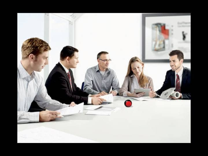 Ein Teammeeting von Brötje Mitarbeitern, vier Männer und eine Frau, an einem großen Tisch sitzend in einem Büro.