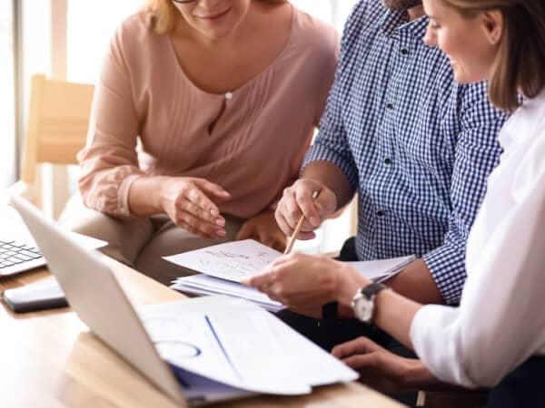 Zwei Frauen und ein Mann sitzen am Schreibtisch vor einem Laptop und diversen Unterlagen und unterhalten sich über ein Projekt.
