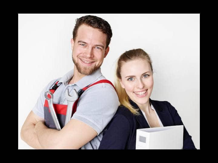 Ein junger Mann in Arbeitshosen, die Arme vor der Brust verschränkt. Und eine junge Frau, klassisch gekleidet mit einem Ordner im Arm. Beide lachen.