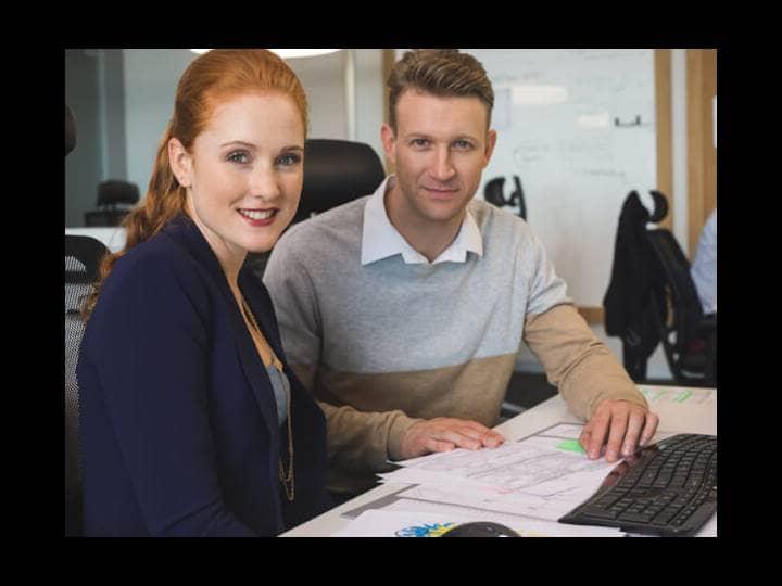 Eine junge Frau und ein junger Mann sitzen zusammen an einem Schreibtisch und lächeln in die Kamera.