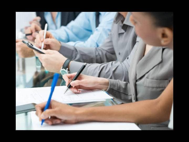 Vier Studenten sitzen nebeneinander an einem Tisch und machen sich Notizen.