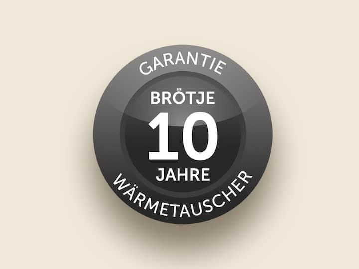 Ein runder, schwarzer Garantiebutton liegt auf hellem Untergrund. Auf dem Button steht Garantie, Brötje 10 Jahre Wärmetauscher.
