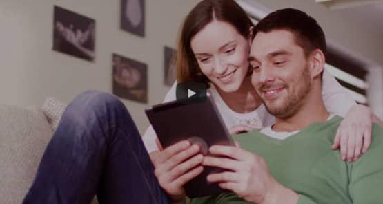 Ein Mann sitzt gemütlich in seiner Wohnung und blickt auf das Tablet in seinen Händen. Dahinter seine Partnerin, die ebenfalls auf das Tablet schaut. Beide lächeln.