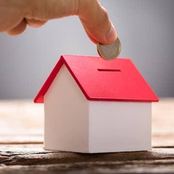 Geld wird in eine Haus-Spardose gesteckt