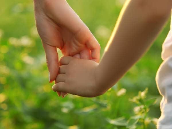 Eine Frauen- und eine Kinderhand. Beide halten sich und gehen über eine Wiese mit Blumen.