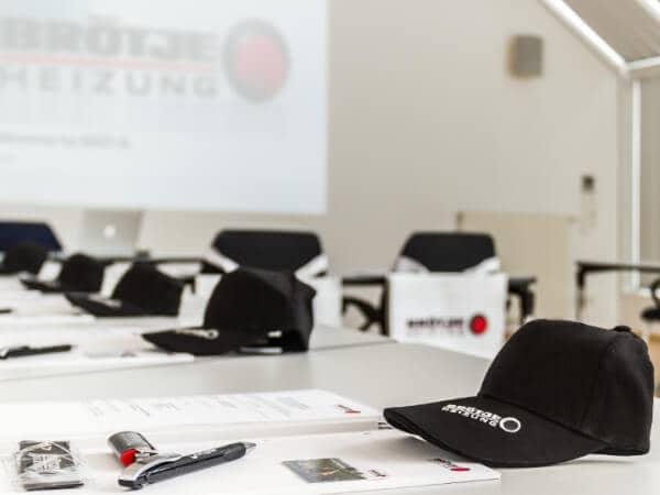 Ein BRÖTJE-Seminarraum mit vorbereiteten, leeren Plätzen mit BRÖTJE-Utensilien und einer BRÖTJE-Präsentation.