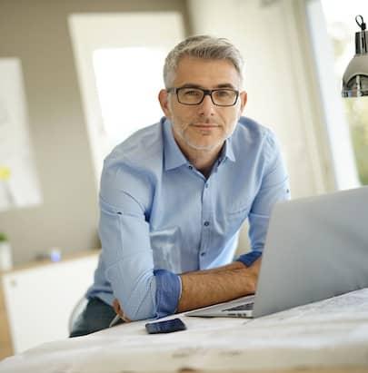 Ein Mann sitzt an einem Tisch, vor sich ein Notebook, und schaut in die Kamera.