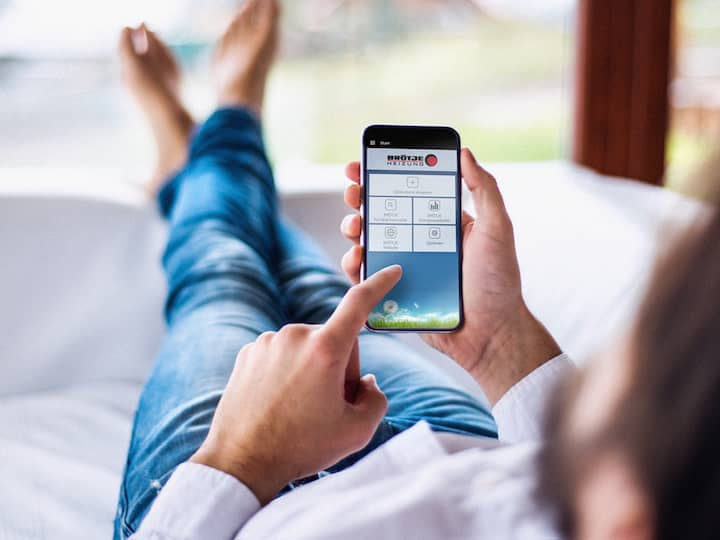 A barefoot figure, dressed in jeans, who is lying down and looking at the Brötje app on their mobile phone.